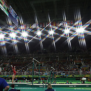 Gymnastics - Olympics: Day 6  Alexandra Raisman #395 of the United States in action on the Uneven Bars watched by her coach Mihai Brestyan during her silver medal performance in the Artistic Gymnastics Women's Individual All-Around Final at the Rio Olympic Arena on August 11, 2016 in Rio de Janeiro, Brazil. (Photo by Tim Clayton/Corbis via Getty Images)<br /> <br /> (Note to editors: A special effects starburst filter used in the creation of this image)