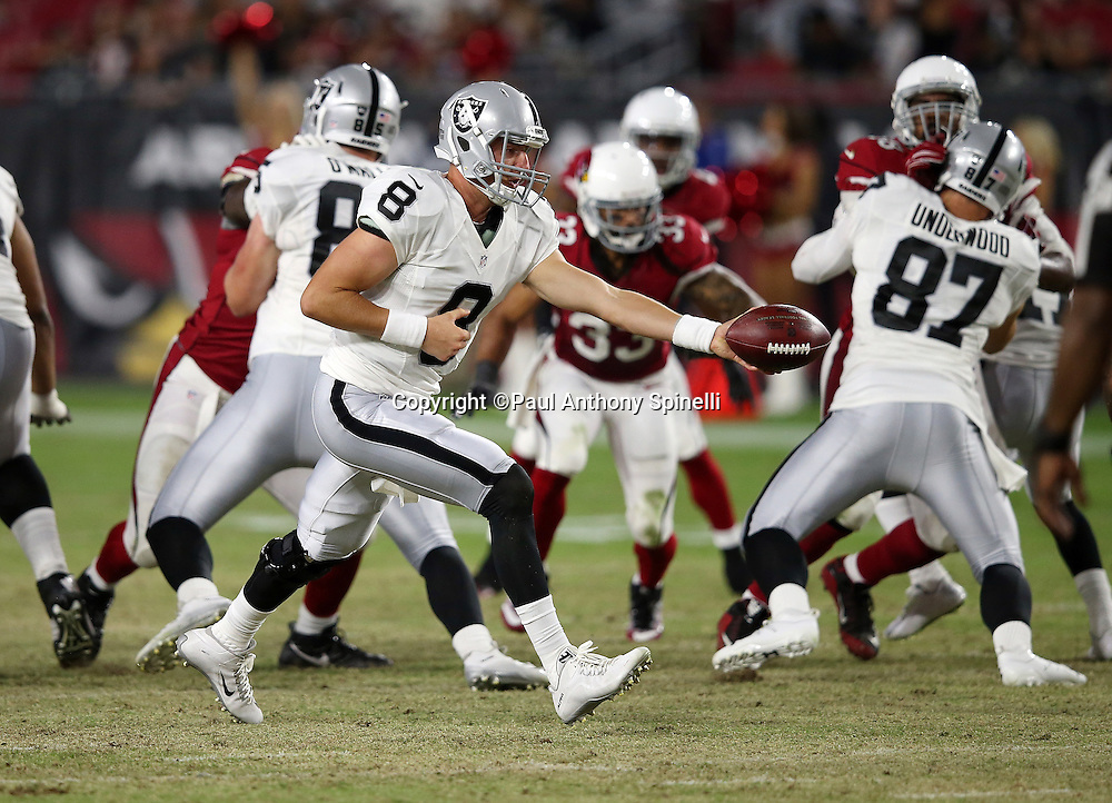 Oakland Raiders quarterback Connor Cook (8) hands off the ball on a running play during the 2016 NFL preseason football game against the Arizona Cardinals on Friday, Aug. 12, 2016 in Glendale, Ariz. The Raiders won the game 31-10. (©Paul Anthony Spinelli)