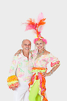 Portrait of happy senior dance couple in Brazilian outfits over gray background