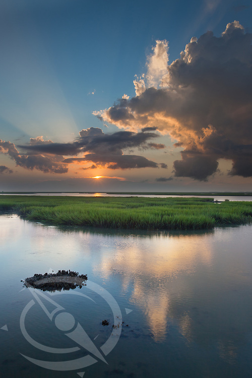 A beacon of light announces the rise of the sun and illuminates the green marsh lands of the South Carolina coast. North Charleston, SC