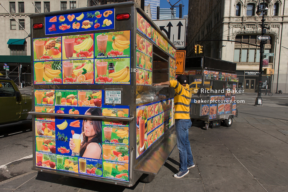 Setting up shop of a kiosk selling multiple varieties of Smoothie fruit drinks on sale on Broadway, New York City. i