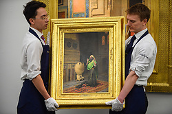 "© Licensed to London News Pictures. 11/10/2019. LONDON, UK. Technicians present ""The Morning Prayer"", by Ludwig Deutsch, (Est GBP0.7-1.0m).  Preview of works from the Najd Collection of orientalist paintings at Sotheby's in New Bond Street, which record daily life in the historic Arab, Ottoman and Islamic worlds  All 155 paintings are on public view 11- 15 October, with 40 works to be auctioned on 22 October.  Photo credit: Stephen Chung/LNP"