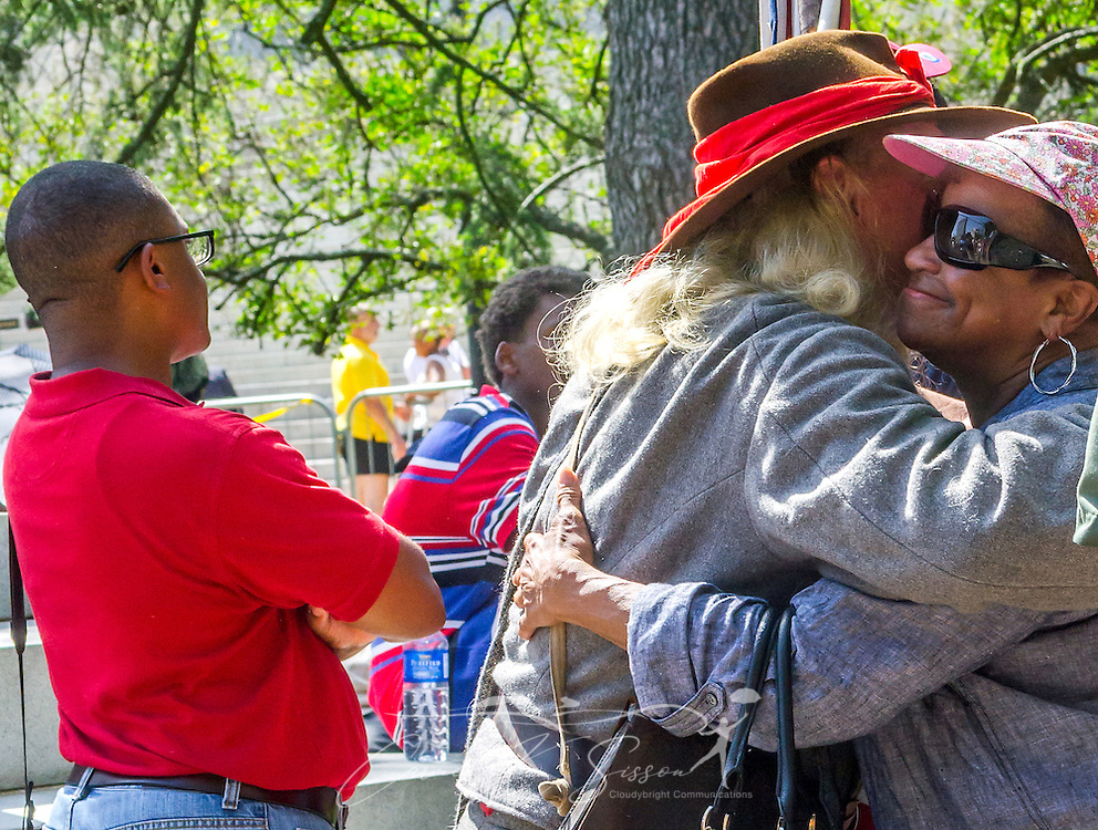 A man dressed as a Confederate soldier and carrying a Confederate flag accepts a hug from an African-American woman, July 10, 2015, in Columbia, S.C. Thousands flocked to the South Carolina Statehouse to see the removal of the  Confederate flag. The flag flew above the capitol dome from 1961-2000, then was moved to the grounds. The flag, which is now permanently removed, will be stored at the Confederate Relic Room and Military Museum. The House voted for its removal after the shooting of nine African-Americans at Emanuel African Methodist Episcopal Church in Charleston, June 17, 2015. Alleged shooter Dylann Roof, who published a manifesto on his website supporting white supremacist beliefs, was seen in numerous photographs holding the Confederate flag. (Photo by Carmen K. Sisson/Cloudybright)