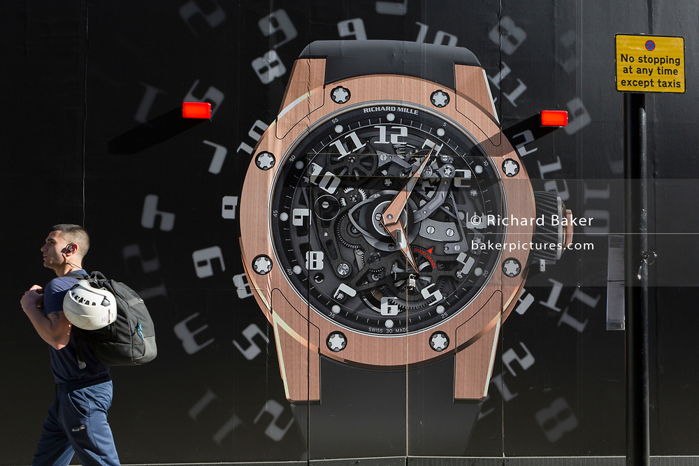 W workman walks past a construction hoarding of a watch outside the new Richard Mille shop in New Bond Street, on 25th February 2019, in London, England.