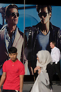 Sexy mens' fashion poster and passing Muslim shoppers at the 2012 Olympic Westfield mall in Stratford, east London.