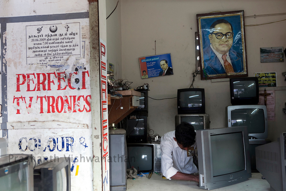 A dalit repair man works at a shop with a picture of D R Ambedkar, at the Tamil Nadu Slum Clearance Board quarters 20 kms away  in Kannagi Nagar in Chennai, India, on Friday, January 14, 2011. Photographer: Prashanth Vishwanathan/HELSINGIN SANOMAT