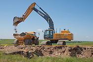 John Deere excavator on dumping dirt on wind project site