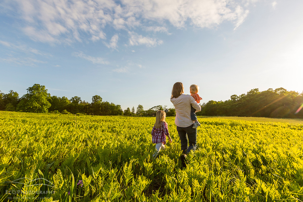 A woman walks in a field with her two young daughters in Epping, New Hampshire.