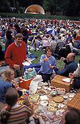Crowds enjoy picnic spreads before an outdoor concert at Kenwood House, North London, on 18th May 1995, in London, England. Set in Hampstead Heath, these grounds were remodelled by Robert Adam between 1764 and 1779. English Heritage host Summer concerts here and families and music fans spend war summer evenings listening to opera, classical or series of themed performances by visiting artists and groups. Here is also the source of one of London's lost rivers, The Fleet which rises here and flows downhill into the city where it becomes part of the sewer system, emerging in the Thames at Blackfriars.