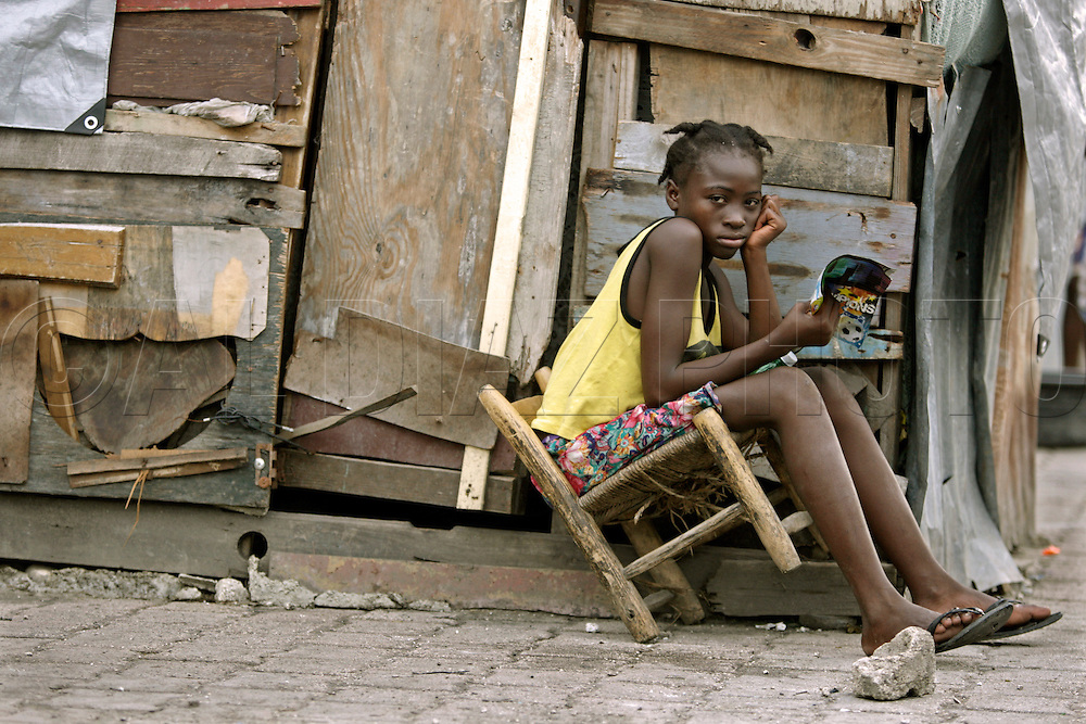 At Champ de Mars camp in downtown Port-au-Prince the temporary tents are becoming a shanty town. Residents use scrap wood to build more permanent structures lined by concrete on the bottom to keep water from infiltrating their home. Here, Johane Fevry, 13, sits by her home reading about soccer on May 25, 2010..