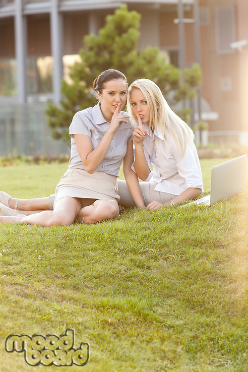 Young businesswomen gesturing silence in office lawn
