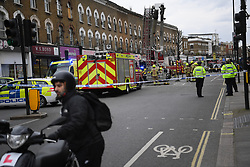 © Licensed to London News Pictures. 01/04/2020. London, UK. In an incident involving all emergency services a suspected COVID-19 case is isolatedand removed from home. Uxbridge Road in Shepherd's Bush was closed for an hour as ambulance, fire brigade and police attended, extracting the patient by crane from a three story apartment building in West London. PPE (personal protective equipment) was in evidence, with the fire brigade using full facerespirators normally reserved for firefighting. A police officercommented the Metropolitan police force are issued only with rubber gloves. Ambulance workers decontaminated the scene and reusable equipment before moving on.  Photo credit: Guilhem Baker/LNP