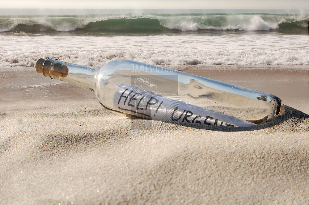 Urgent help message in a clear glass bottle emerging from the sand of an ocean beach
