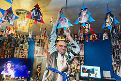 Shaun Smith, 52, from Basildon in Essex adjusts one of the hanging Christmas trees he made himself in his sitting room. He has built up a huge £7,000 collection of Cheryl Cole memorabilia in the space of about eight months after she impressed him in a music video he was watching.. PLACE, January 24 2019.