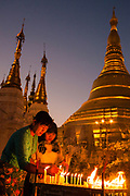 A Burmese woman and girl pay hommage to the Buddha with candles at Shwedagon Pagoda before sunrise in Yangon, Myanmar. A main attraction of this capital city, Shwedagon is said to house relics of the four previous Buddhas.