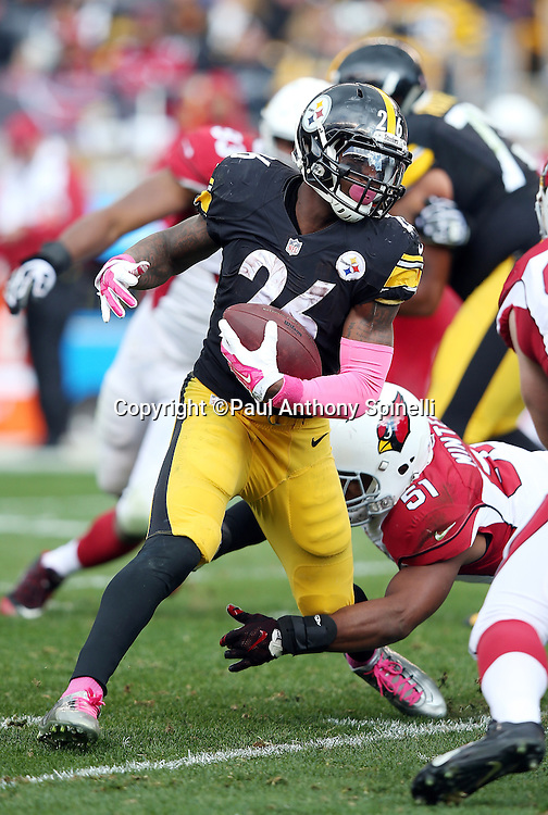 Pittsburgh Steelers running back Le'Veon Bell (26) tries to break free from a tackle attempt by Arizona Cardinals inside linebacker Kevin Minter (51) as he runs the ball during the 2015 NFL week 6 regular season football game against the Arizona Cardinals on Sunday, Oct. 18, 2015 in Pittsburgh. The Steelers won the game 25-13. (©Paul Anthony Spinelli)