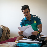 PALM SPRINGS, FLORIDA, JANUARY 14, 2018<br /> Mamudul Hasson, 21, looks at notebooks and items he carried with him on the mattress he sleeps on next to  his uncle in his house. Hassan is a Rohingya Muslim refugee who just arrived to the United States three weeks ago.<br /> (Photo by Angel Valentin/Freelance)