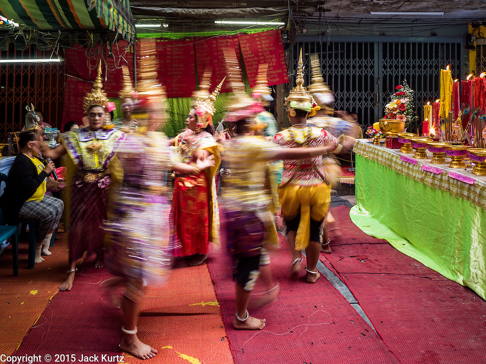 """21 DECEMBER 2015 - BANGKOK, THAILAND: Thai classical dancers perform during the annual rededication of a community Buddhist shrine in Pak Khlong Talat, also called the Flower Market. The market has been a Bangkok landmark for more than 50 years and is the largest wholesale flower market in Bangkok. A recent renovation resulted in many stalls being closed to make room for chain restaurants to attract tourists. Now Bangkok city officials are threatening to evict sidewalk vendors who line the outside of the market. Evicting the sidewalk vendors is a part of a citywide effort to """"clean up"""" Bangkok.       PHOTO BY JACK KURTZ"""