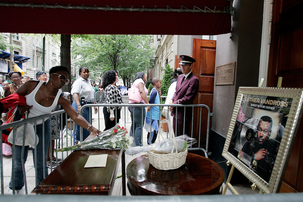 A Fan of R&B singer-songwriter Luther Vandross puts flowers on a table outside the wake in New York Wednesday, 06  July, 2005 Vandross died on July 1, two years after suffering a serious stroke..