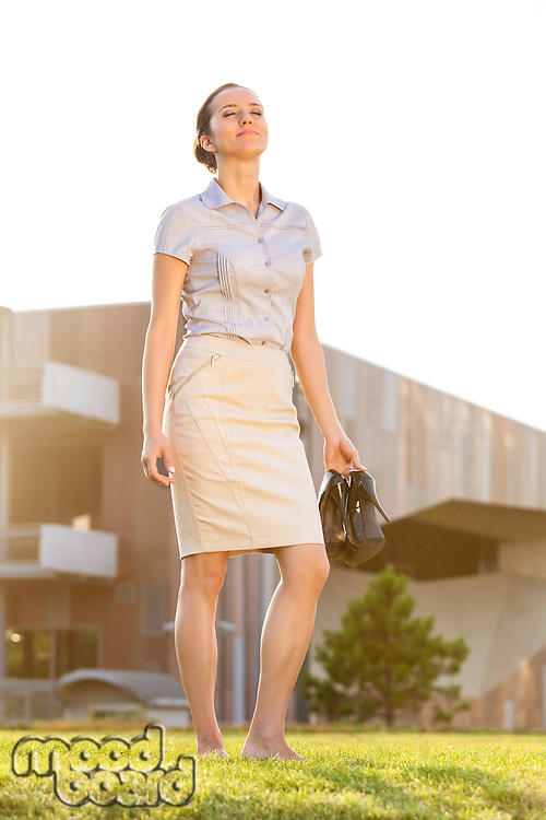 Relaxed young businesswoman holding footwear in office lawn