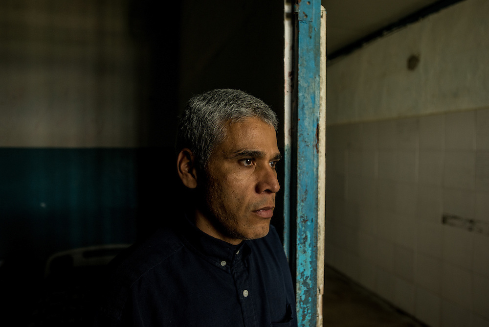 BARQUISIMETO, VENEZUELA - JULY 29, 2016: Mario Carrusí, 41, poses for a portrait at the entrance to his hospital room. Mr. Carrusí is a schizophrenic who has also been diagnosed with mystical religious delusions. In 1998, before he was diagnosed, he killed his mother by decapitating her.  The nursing staff at the hospital fears that he could become violent again because he does not always have all the medications that he needs.  Carrusí has since become a devout evangelical Christian. PHOTO: Meridith Kohut