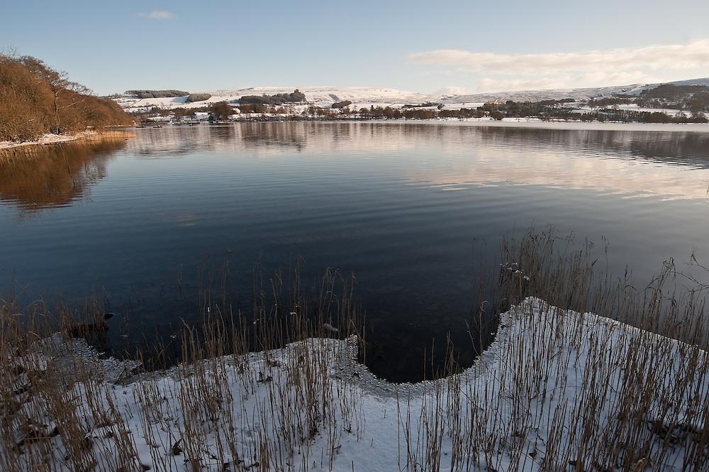 Ullswater in winter, Pooley Bridge, frozen ice on the lake, blue sky, snow.