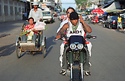 October 2004 - Phnom Penh; Cambodia - Chhin Toeun; 24; or Hawaii to his friends; rides around central Phnom Penh with his friend So Chamroeun; 32; or Charlie. Boredom is a big factor for these guys who spend a lot of time cruising the city on large dirt bikes. After escaping the Khmer Rouge regime to the US as refugees; many young American Cambodians are being sent back to Cambodia never to return to the US again. A new policy in 2002 meant that any US-Cambodian who still had not applied for US citizenship and had been convicted of a felony would be deported back to Cambodia after living in the US all their life. Over 1; 400 convicted felons are proposed to be sent back in the next few years and naturally the re-adjustment to a life they don't know or understand is a difficult one. Photo Credit: Luke Duggleby