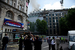 © Licensed to London News Pictures. LONDON, UK  14/06/11. Smoke pours from the roof of a building on fire on Aldwich in London today (Tuesday) as members of the public watch on and take pictures. Please see special instructions for usage rates. Photo credit should read Matt Cetti-Roberts/LNP