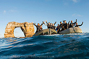 Scuba divers from the Galapagos Sky pose next to Darwins's Arch offshore Darwin Island, Galapagos, Ecuador.