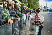 29 MAY 2014 - BANGKOK, THAILAND: Thai soldiers accept water from a woman while they line the road around Victory Monument. After a series of protests around Victory Monument earlier in the week, the Thai army Thursday shut down vehicle access to the area, one of the main intersections in Bangkok, and kept people out of the area. Thousands of soldiers surrounded the Monument and effectively locked the area down. There were no protests at Victory Monument for the first time in the week since the coup deposed the elected civilian government.   PHOTO BY JACK KURTZ