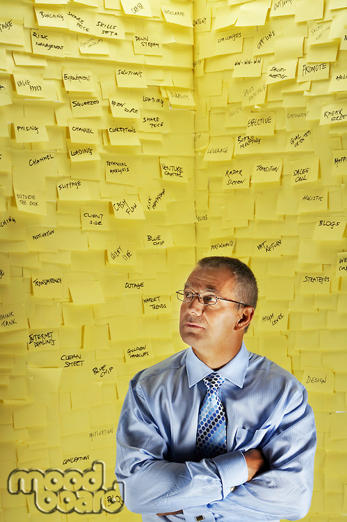 Middle-aged man in glasses standing in front of wall covered in sticky notes