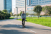 Young man on an Electric kick scooter on a bicycle path. Photographed in Ramat HaHayal, Tel Aviv, Israel