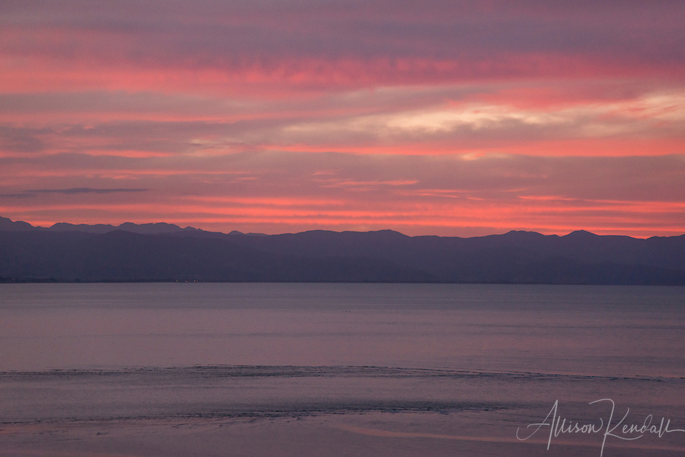 A vivid sunset paints the evening sky with pink and lavender color over the Tasman Bay and coast of Nelson, New Zealand