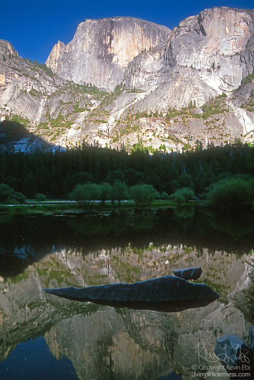 Half Dome, one of the most famous peaks in Yosemite National Park, California, is reflected in the calm waters of mirror lake just before sunset.