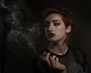 Moody portrait of woman with cigarette in dark bar.