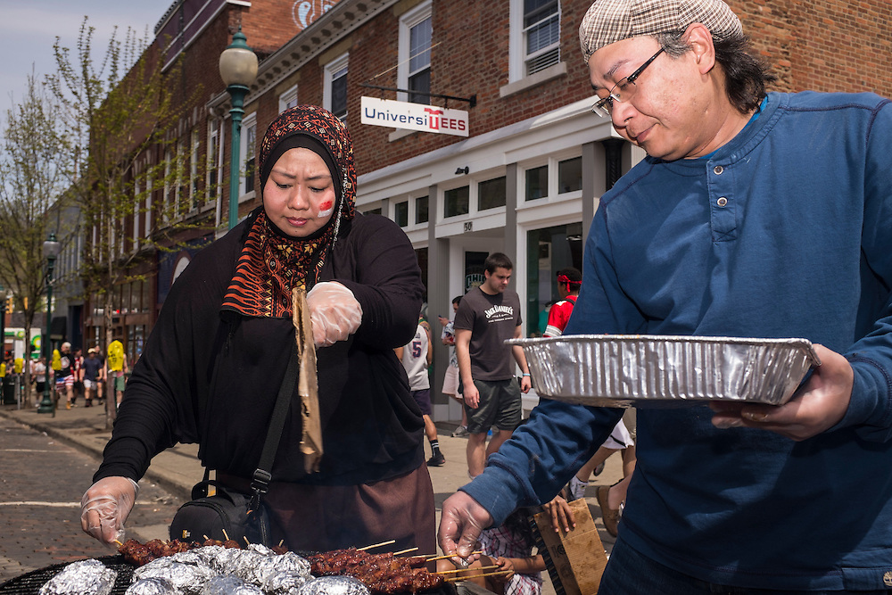 Manska Intan Sari, left, and Airlangga Dermawan work the grill for the Indonesian Students Association table at the International Street Fair on Saturday, April 18, 2015.  Photo by Ohio University  /  Rob Hardin