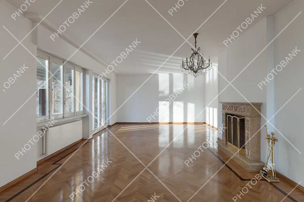 interior of an house, empty room with fireplace, parquet floor and white walls