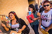"""25 AUGUST 2012 - PHOENIX, AZ:  A girl fans herself while she and her friends wait to get into the deferred action workshop in Phoenix. Hundreds of people lined up at Central High School in Phoenix to complete their paperwork to apply for """"Deferred Action"""" status under the Deferred Action for Childhood Arrivals (DACA) program announced by President Obama in June. Volunteers and lawyers specialized in immigration law helped the immigrants complete the required paperwork. Under the program, the children of undocumented immigrants brought to the US before they turned 16 years old would not be subject to deportation if they meet a predetermined set of conditions.    PHOTO BY JACK KURTZ"""