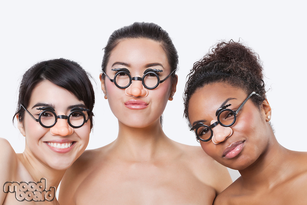 Portrait of young multi-ethnic women wearing groucho glasses over white background