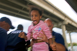 29 August, 2005. New Orleans, Louisiana.<br /> Hurricane Katrina hits New Orleans. Rescue workers frantically search for survivors in the rising flood waters of the 9th ward, bringing them to relevant safety on the elevated section of I-10. A young resident is delighted to be rescued from her submerged home. <br /> Photo; Charlie Varley.
