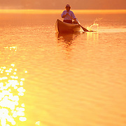 Woman paddling a canoe at sunrise on Damariscotta Lake in northern Maine.