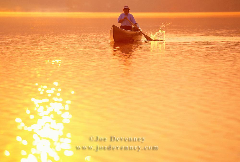 Woman paddling a canoe at sunrise on Damariscotta Lake in northern Maine.