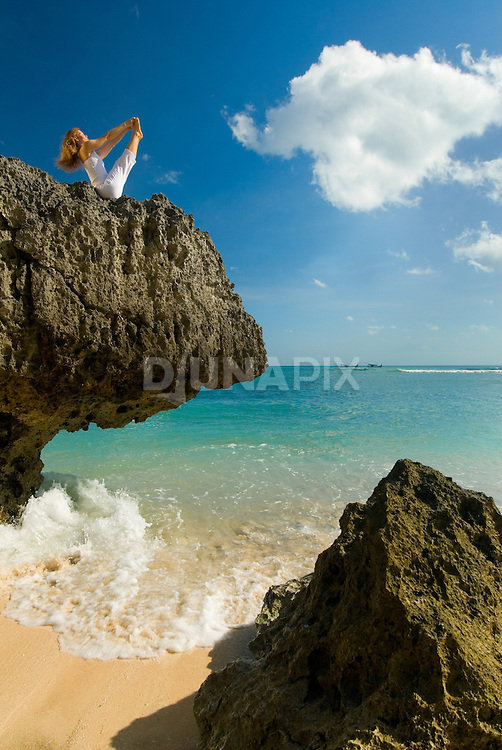 A woman performs yoga on a sheer rock outcrop over a tropical beach, Bali, Indonesia. Yoga photography by Djuna Ivereigh.