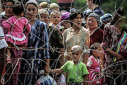 Ethic Uzbek refugees walk behind a barbed wire fence as they queue to return to Kyrgysztan at a border crossing some seven kilometres from the city of Osh, Kyrgyzstan, on 18 June 2010. Although there were no new reports of fighting on 18 June the refugee situation sparked by the recent violence continued, with tens of thousands of members of the Uzbek minority trying to flee into Uzbekistan while other ethnic Uzbeks trusting the currently calm situation decided to return to their homes in Kyrgyzstan.