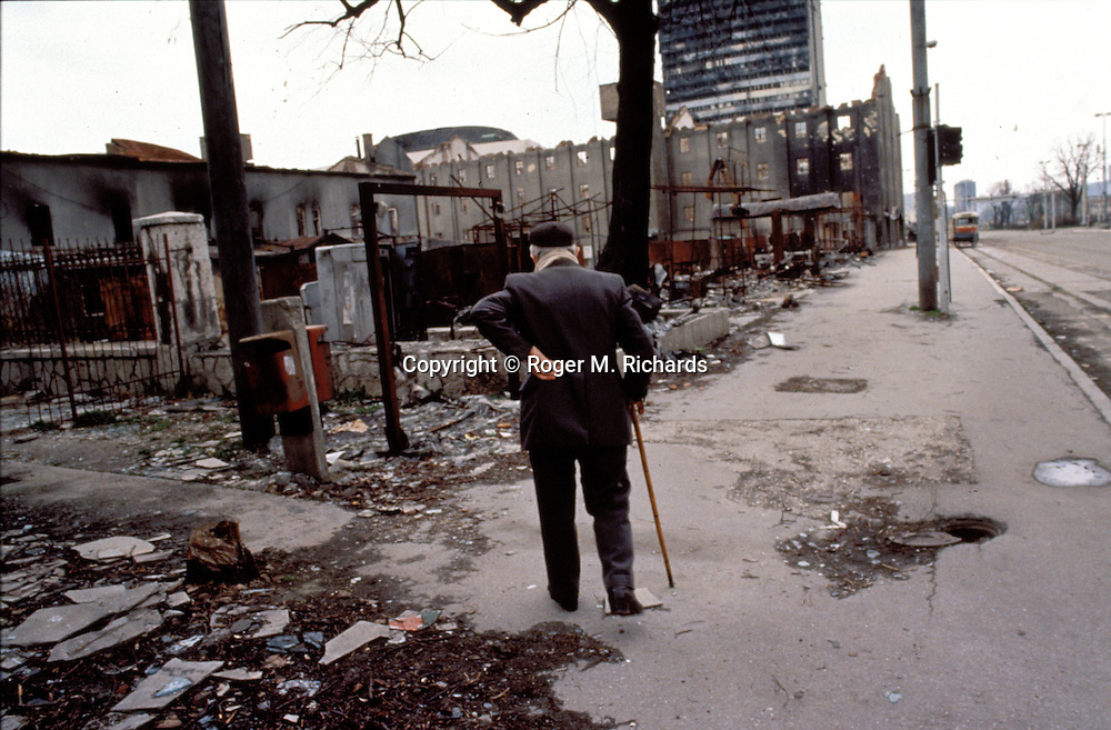 An old man walks amid the ruins of Sarajevo in April 1993, exactly one year after the Bosnian Serb siege of the city began. At right is the infamous 'Sniper Alley'. (Photo by Roger Richards)