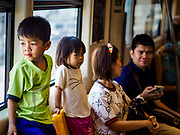 06 DECEMBER 2018 - SAMUT PRAKAN, THAILAND:  Children ride the new east extension of the BTS Skytrain on the opening day of the extension. The 12.6 kilometer (7.8 miles) east extension of the Sukhumvit Line of the Bangkok BTS Skytrain goes into Samut Prakan, a town east of Bangkok.  The system is now 51 kilometers long (32 miles), including the 12.6 kilometer extension that opened December 06. About 900,000 people per day use the BTS.      PHOTO BY JACK KURTZ