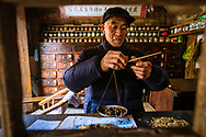 An apothecary prepares medicines from herbs in the rural village of Shang Li near to Ya'an in Sichuan Province, China.<br /> Picture date: Thursday April 5, 2018.<br /> Photograph by Christopher Ison &copy;<br /> 07544044177<br /> chris@christopherison.com<br /> www.christopherison.com