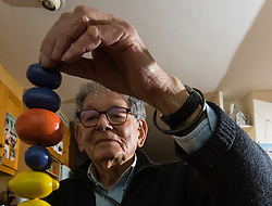 Retired product designer turned toy maker, whose many innovations became iconic household names Tom Karen is photographed with toys he created from recycled materials at his home in Cambridge, UK. <br /> PICTURED: Tom demonstrates his puzzle that allows children to explore colour, patterns and numbers.<br /> Cambridge, March 01 2018.