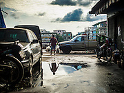 02 SEPTEMBER 2015 - BANGKOK, THAILAND: A man passes a puddle in the Bang Chak Market. The Bang Chak Market serves the community around Sois 91-97 on Sukhumvit Road in the Bangkok suburbs. About half of the market has been torn down, vendors in the remaining part of the market said they expect to be evicted by the end of the year. The old market, and many of the small working class shophouses and apartments near the market are being being torn down. People who live in the area said condominiums are being built on the land.         PHOTO BY JACK KURTZ