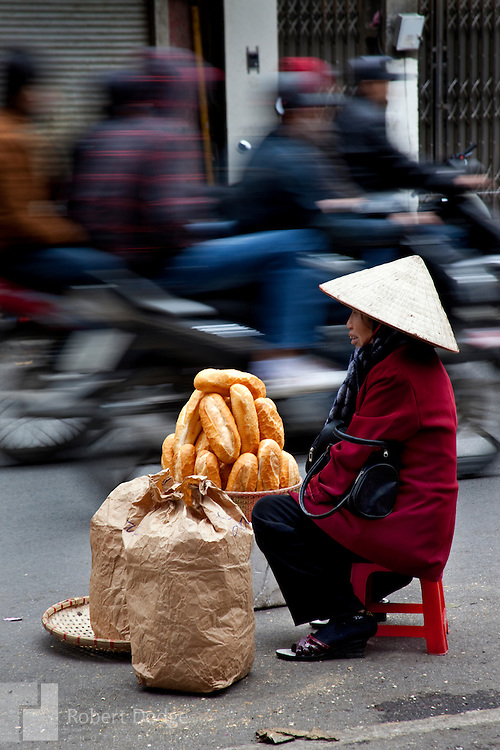 A Hanoi woman sells French baguettes in an image that tells the history of Vietnam. Traditional roles for women, the French occupation, western fashions and fast-paced motorbikes all tell the story of Vietnam's development from ancient Asia to modern Asian Tiger. Robert Dodge, a Washington DC photographer and writer, has been working on his Vietnam 40 Years Later project since 2005. The project has taken him throughout Vietnam, including Hanoi, Ho Chi Minh City (Saigon), Nha Trang, Mue Nie, Phan Thiet, the Mekong, Sapa, Ninh Binh and the Perfume Pagoda. His images capture scenes and people from women in conical hats planting rice along the Red River in the north to men and women working in the floating markets one the Mekong River and its tributaries. Robert's project also captures the traditions of ancient Asia in the rural markets, Buddhist Monasteries and the celebrations around Tet, the Lunar New Year. Also to be found are images of the emerging modern Vietnam, such as young people eating and drinking and embracing the fashions and music of the west.
